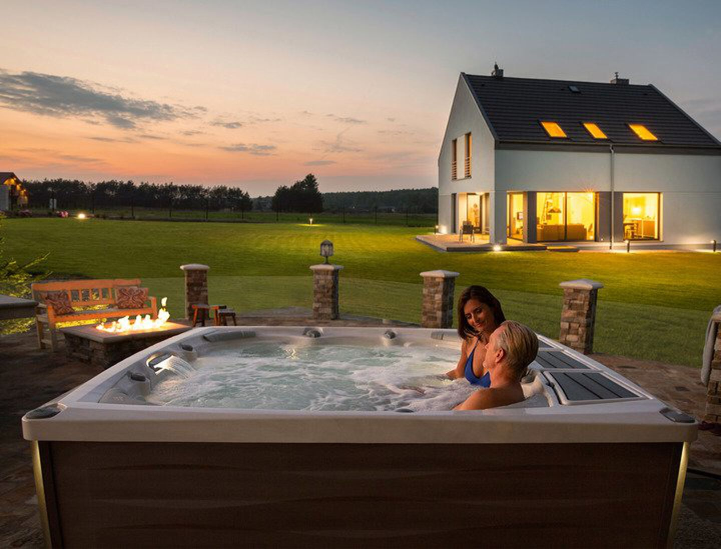 Couple in hot tub at sunset